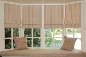 Roman blinds in the bay with window seat cushion in coordinating fabric.