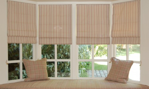Bespoke roman blinds in ticking stripe fabric with window seat and cushions in room overlooking garden