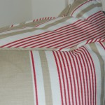 Close up photo of cushions in red and beige striped ticking fabric