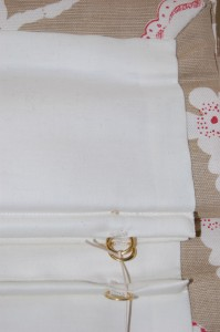 Rod pockets are not sewn through to the face fabric on roman blinds made by Diana Murray Interiors so you will not see a line of stitches at the front.