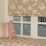 Photo of window seat cushion and piped scatter cushions in french ticking. Roman blind above in floral fabric.