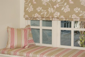 A bespoke window seat cushion and scatter cushions in french ticking fabric with roman blind above.