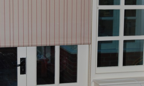 Photo of roller blind in red striped fabric over a set of french doors