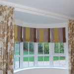Photo showing five roman blinds in a bay window and non working curtains to frame the window