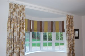 Five bespoke roman blinds with dress curtains.