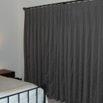 Photo showing a set of full length hand made curtains in a brown geometric fabric.