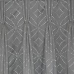 Photo showing an image of a triple pleat hand sewn curtain heading on geometric fabric