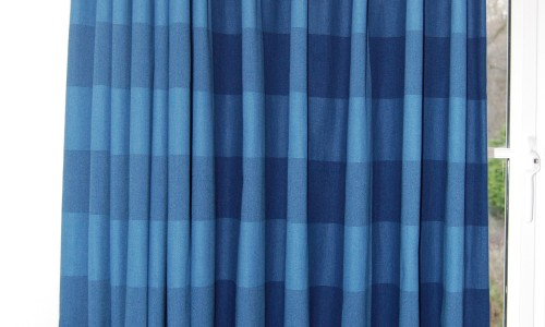 Photo of curtain in blue checked fabric with curtain half open and half closed to show effect on the design