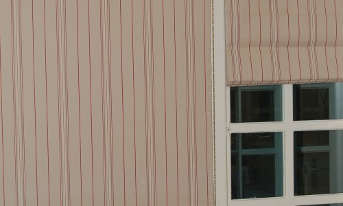 Photo showing a roller blind made up in a customer's own red and beige striped fabric which matches roman blinds in the same room
