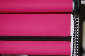 Photograph of a roller blind in a bright pink plain fabric with black piping along bottom bar