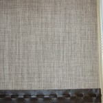 Photograph of a roller blind with a leather style trim across bottom edge